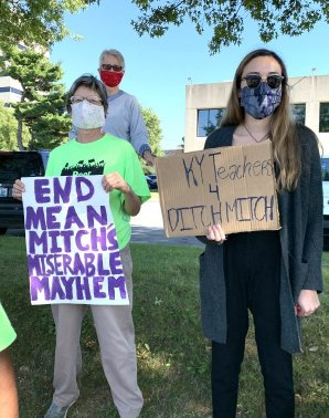 "two protestors stand outside Mitch McConnell's office with signs that read ""end mean Mitch's miserable mayhem"" and ""KY Teachers 4 ditch Mitch"""